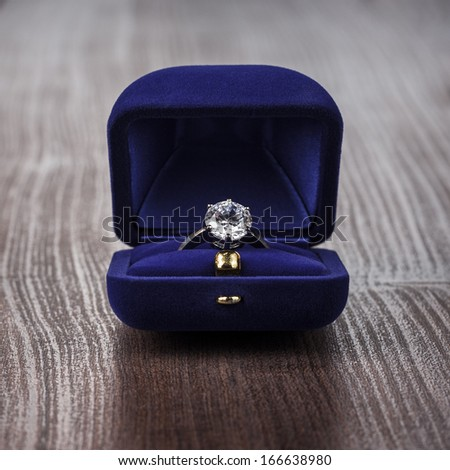 ring in the box on wooden table - stock photo
