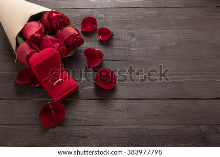 Ring is beside of the red roses flower on the wooden background.