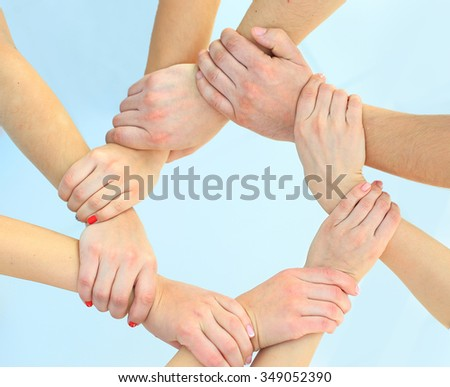 Ring of hands teamwork showing your product - stock photo