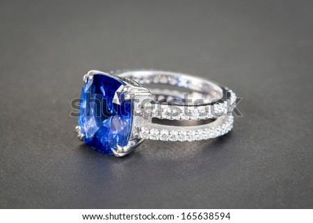 Ring of the jewelry with dark blue sapphire on the black background - stock photo
