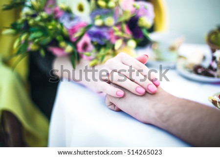 Ring on a finger near a bouquet of flowers