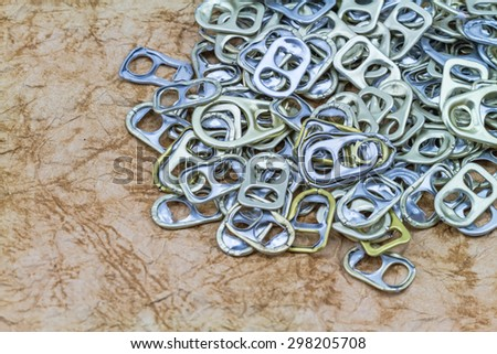 Ring pull aluminum of cans on grunge paper sheet background - stock photo