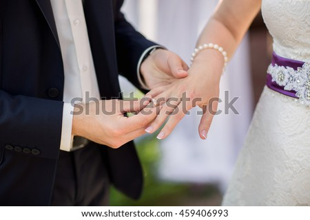 Ring. Wedding rings. Hands of bride and groom in solemn process of exchanging rings, symbolizing the creation of new happy family. Groom putting a ring on bride's finger during wedding ceremony