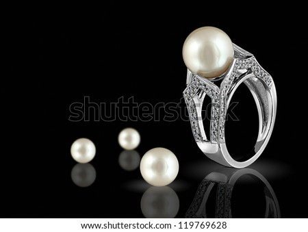 Ring with pearl and diamonds on black background - stock photo