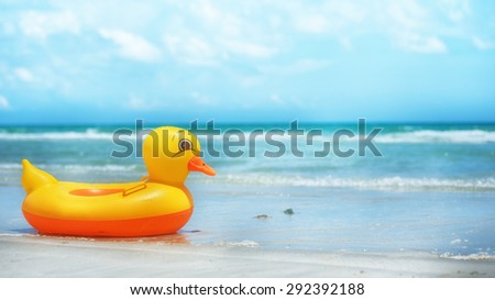 Ring yellow duck on the beach. - stock photo