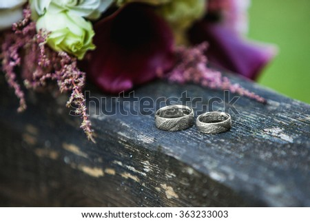rings and bouquet on a wooden table