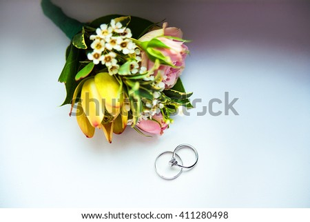 rings and flowers. Groom's boutonniere closeup. Wedding boutonniere of roses. - stock photo