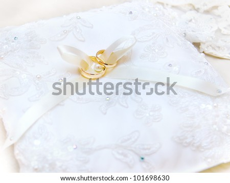 Rings on a pillow for wedding. Close up Wedding rings on white bow. Wedding card for your invitation