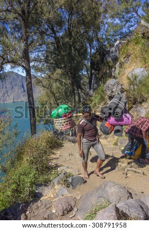 RINJANI MOUNTAIN, LOMBOK, INDONESIA-JUNE 11,2015: Unidentified mountain porters carry food necessities walks slowly on trekking path on the way to Rinjani Mountain in Lombok, Indonesia. - stock photo