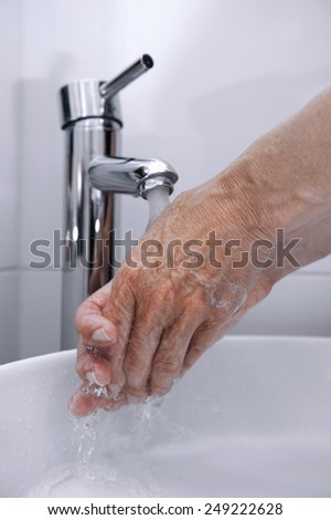 Rinse hands under a faucet with the water falling