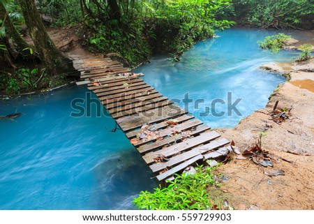 Rio celeste and small wooden bridge Tenorio national park Costa Rica