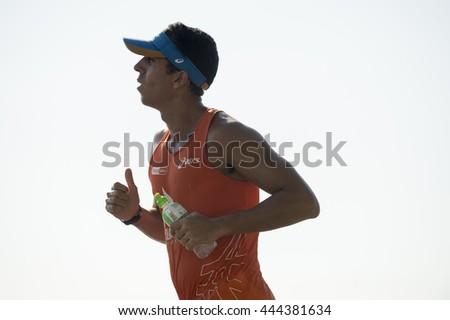 RIO DE JANEIRO - APRIL 3, 2016: Carioca Brazilian man jogs against the bright morning sky in Copacabana, a popular destination for early morning recreation.  - stock photo