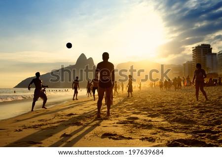 Rio de Janeiro beach football silhouettes of Brazilians playing keepy uppy altinho soccer on the sunset shore at Posto Nove Ipanema Beach - stock photo