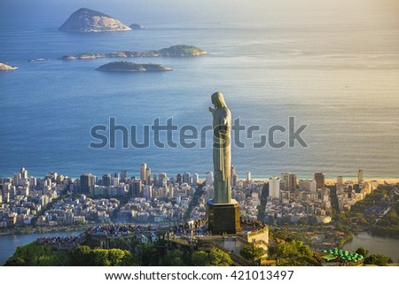 RIO DE JANEIRO, BRAZIL - FEBRUARY 2016: Aerial view of Christ The Redeemer Statue with people visiting Corcovado Hill. View from helicopter through Ipanema Beach.