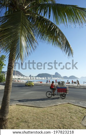 RIO DE JANEIRO, BRAZIL - FEBRUARY 03, 2014: Brazilian man delivering cooler and chairs to beach kiosk on a tricycle at Copacabana Beach.