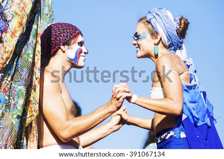 Rio de Janeiro, Brazil - February 9, 2016: Happy couple smiling, holding hands and wearing colourful costumes and face paint during Orquestra Voadora parade at Carnaval 2016 in Rio de Janeiro, Brazil. - stock photo