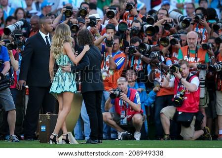 RIO DE JANEIRO, BRAZIL - July 13, 2014: Brazilian model Gisele Bundchen and former Spanish player Carles Puyol at the World Cup closing ceremony at Maracana Stadium. NO USE IN BRAZIL. - stock photo