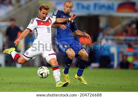 RIO DE JANEIRO, BRAZIL - July 13, 2014: Mascherano of Argentina and Goetze of Germany compete for the ball during the World Cup Final game at Maracana Stadium. NO USE IN BRAZIL. - stock photo