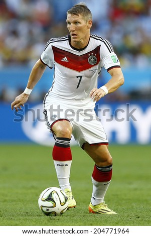 RIO DE JANEIRO, BRAZIL - July 13, 2014: Schweinsteiger of Germany kicks the ball during the 2014 World Cup Final game between Argentina and Germany at Maracana Stadium. NO USE IN BRAZIL.  - stock photo