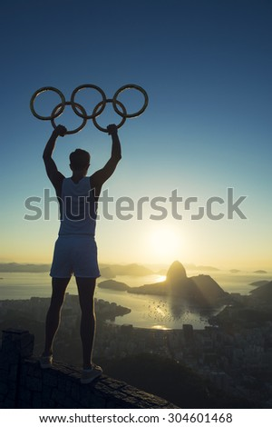 RIO DE JANEIRO, BRAZIL - MARCH 05, 2015: Man stands in silhouette holding Olympic rings above city skyline view of Sugarloaf Mountain and Guanabara Bay at sunrise. [illustrative editorial]