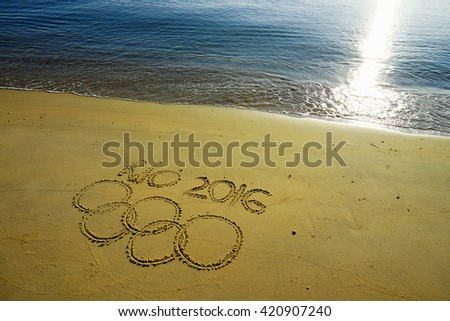 RIO DE JANEIRO, BRAZIL - MAY 10, 2016: Olympic rings drawn in the sand under Rio 2016 message on May 10, 2016 in the beautiful beach, Brazil. - stock photo