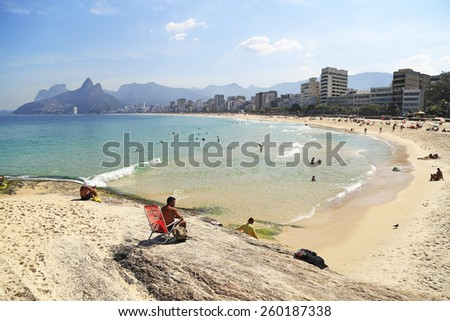 Rio de Janeiro, Brazil - May, 5 2014:  Tourists and locals enjoying themselves at Ipanema Beach on a beautiful summer day. This view is towards the west with Two Brothers Mountain in the background. - stock photo