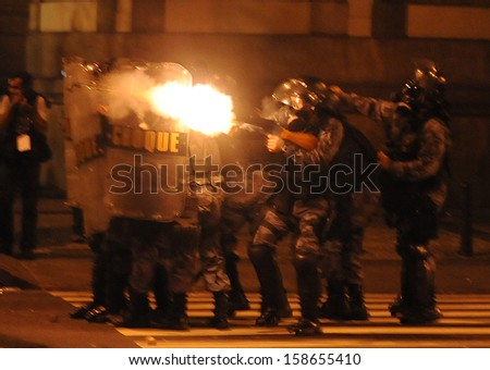 RIO DE JANEIRO, BRAZIL - OCTOBER 15: Anti- riot police battalion fire pepper gas bombs against demonstrators along the city center main avenue, Rio Branco, in support to the teacher's strike as the annual October 15 Teachers' Day holiday came to a violent