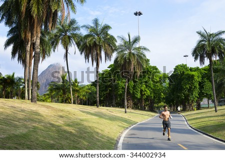 RIO DE JANEIRO, BRAZIL - OCTOBER 17, 2015: Brazilian jogger runs in front of a view of Sugarloaf Mountain on the bike path at the Aterro do Flamengo Park, a popular recreational destination.  - stock photo