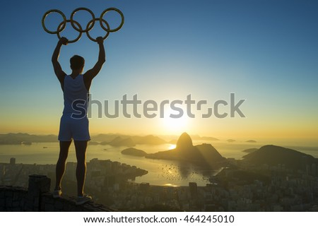 RIO DE JANEIRO - MARCH 5, 2015: Athlete stands in silhouette holding Olympic rings above a skyline view of Sugarloaf Mountain and Guanabara Bay in celebration of the city hosting the Summer Games.