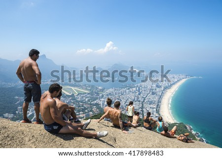 RIO DE JANEIRO - MARCH 9, 2016: Visitors take in the view of the city skyline after a hike to the top of Two Brothers Mountain, overlooking Ipanema Beach.
