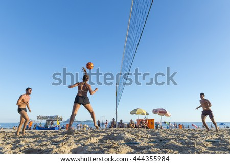 RIO DE JANEIRO - MARCH 17, 2016: Young carioca Brazilian men and women play a game of futevolei (footvolley), a sport that combines football/soccer and volleyball, on Ipanema Beach.  - stock photo