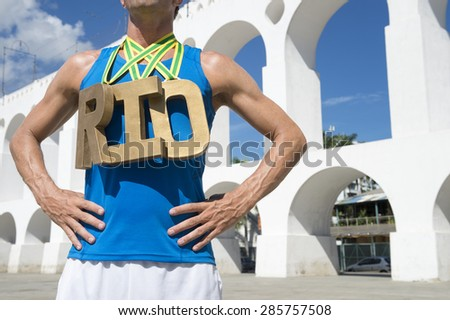 RIO 2016 first place athlete wearing gold medals standing at Arcos da Lapa Arches Rio de Janeiro Brazil  - stock photo