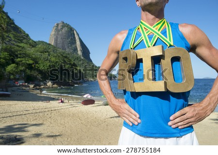 RIO first place athlete wearing gold medals standing outdoors in front of Sugarloaf Mountain Rio de Janeiro Brazil  - stock photo