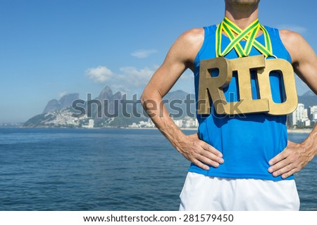 RIO first place athlete wearing gold medals standing outdoors in front of the sea at Ipanema Beach Rio de Janeiro Brazil  - stock photo