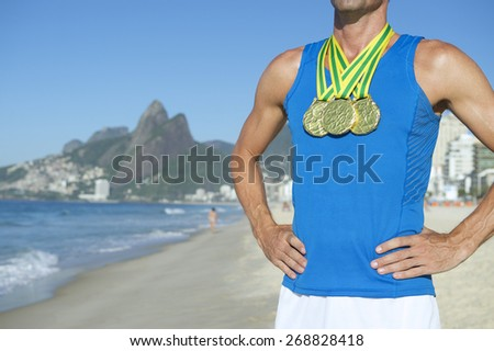 Rio 2016 first place athlete wearing gold medals standing outdoors on Ipanema Beach Rio de Janeiro Brazil  - stock photo