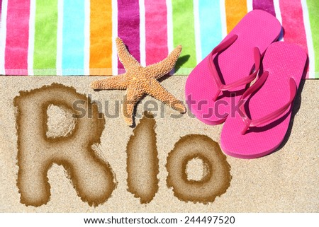 Rio. Overhead view ot the word RIO written on beach sand with a colorful striped towel, pink thongs and a starfish conceptual of a summer vacation and travel in Rio de Janiero, Brazil - stock photo