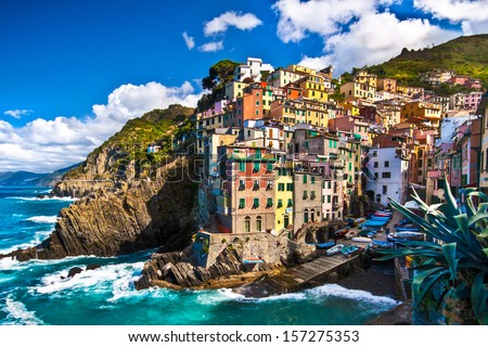 Riomaggiore fisherman village in a dramatic windy weather. Riomaggiore is one of five famous colorful villages of Cinque Terre in Italy, suspended between sea and land on sheer cliffs.