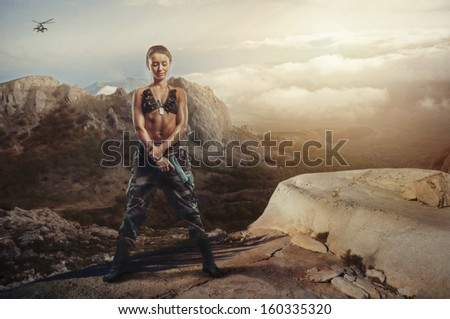 Riot girl on a rocky ledge with a gun - stock photo