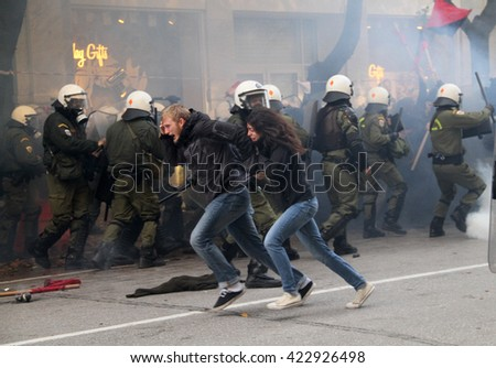 Riot police officers arrest youths during renewed clashes in the city centre streets on December 06, 2004 in Thessaloniki, Greece.  - stock photo