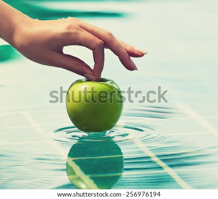 Ripe and juicy green Apple in his hands above the water .The benefits of vitamins - stock photo