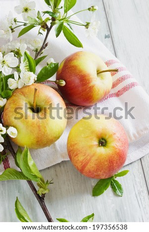 ripe apple and blossoming branch on a wooden background. selective focus - stock photo