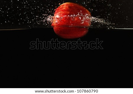 Ripe apple falling into the water with a splash on a dark background closeup - stock photo