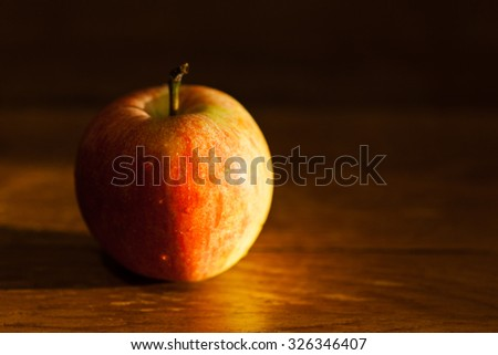ripe apple fruit on wooden table illuminated by afternoon sunlignt