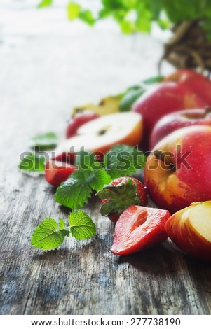 ripe apples and strawberries on old wooden table. fresh fruit from the garden. health and diet food. selective focus - stock photo
