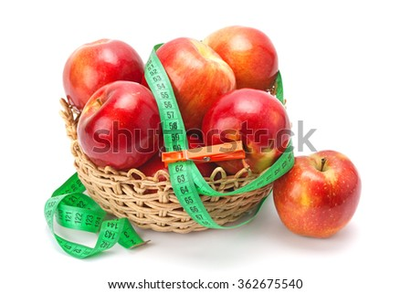 Ripe apples arranged in a basket and measuring tape isolated on white. Concept for health, diet. - stock photo