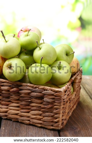 Ripe apples in basket on table on natural background - stock photo