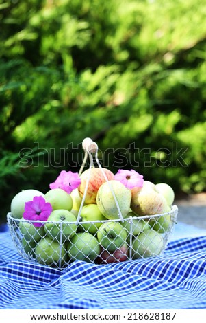 Ripe apples in basket outdoors