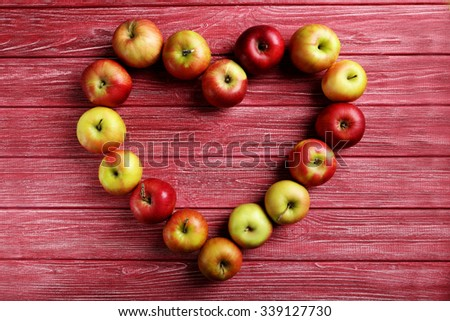Ripe apples on a red wooden table - stock photo