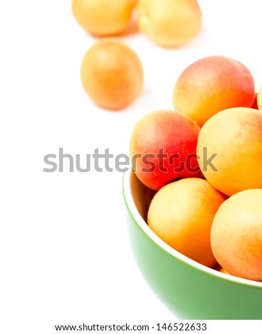Ripe apricots in a ceramic bowl on a white background.