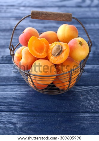Ripe apricots on metal basket on wooden table close up - stock photo